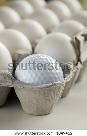 Golf ball and eggs in an egg carton
