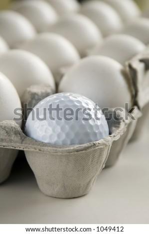 Golf ball and eggs in an egg carton - stock photo
