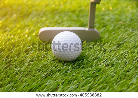 Golf ball and golf club putt on green grass - stock photo