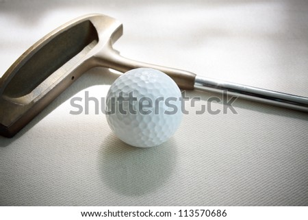 golf ball and putter lied on white floor - stock photo