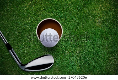 Golf ball and putter on green grass  - stock photo