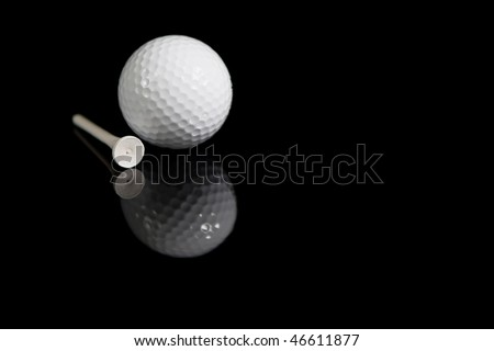 Golf Ball and Tee on black background with reflection - stock photo