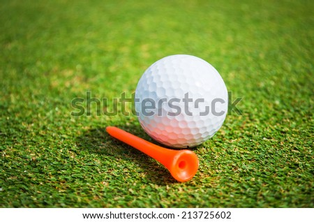 golf ball and tee on green - stock photo
