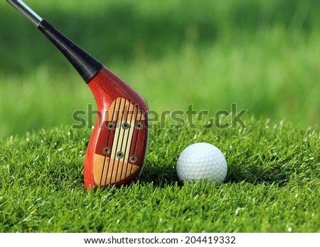 Golf ball and Wooden Driver on green grass background