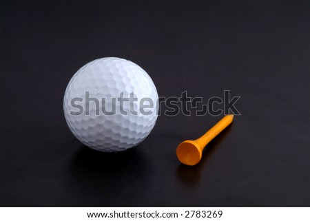 Golf ball and yellow, wooden tee on black background
