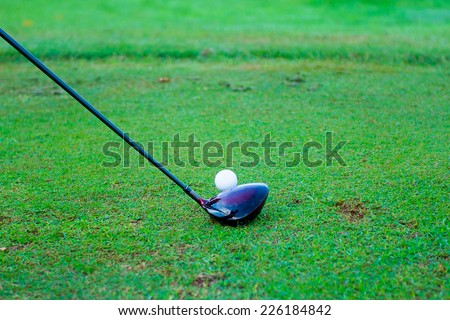 Golf ball behind driver at driving range, plenty of copy-space and very shallow depth - stock photo