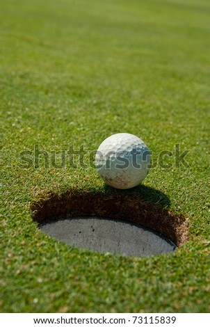 Golf ball extremely close to the hole - stock photo