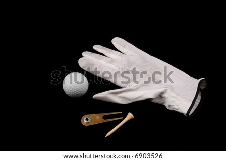 golf ball, glove, divot tool and tee on black background - stock photo