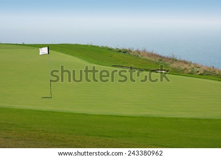 Golf ball in a green course and hole - stock photo