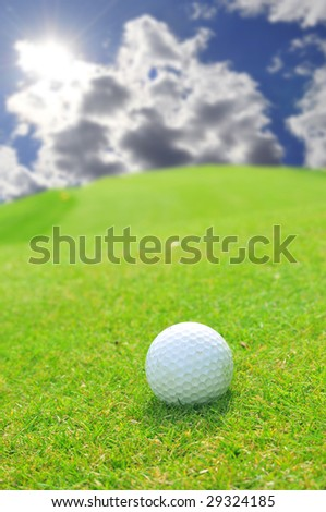 Golf ball in green grass with sunny bright sky in the background