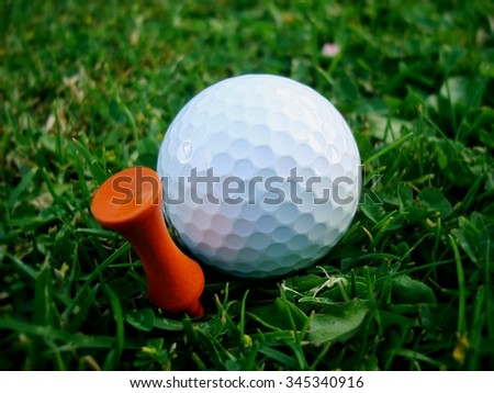 Golf Ball just just behind orange tee with ball slightly blurred for effect - stock photo