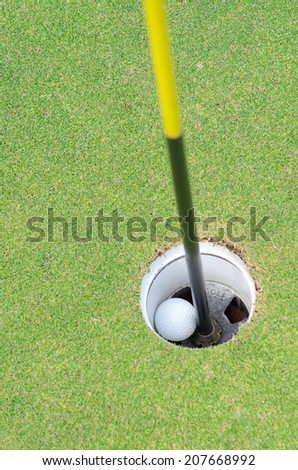 Golf ball move to the hole, hole in one shot. - stock photo
