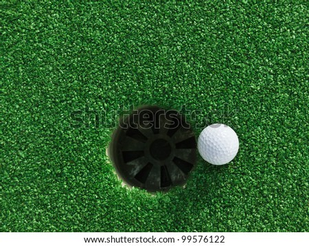 Golf ball near the hole - stock photo