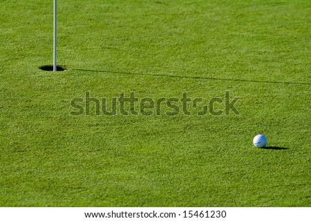 golf ball near the hole on a putting field - stock photo