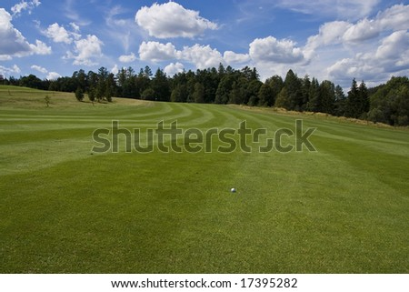 golf ball on a fairway of a beautiful golf course with dramatic summer sky - stock photo