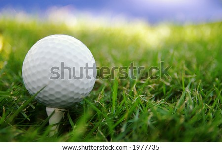 Golf ball on a tee, and sky - stock photo