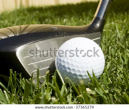 Golf ball on a tee with a driver