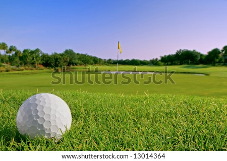 golf ball on bunker above flag and green on tropical course in morning - stock photo