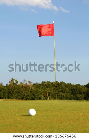 Golf ball on field with red flag in background. Vertical shot.