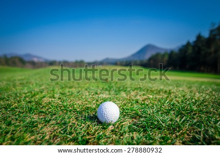 Golf ball on green area with green grass ahead and mountains in background. Nice sunny summer or spring day. Wide angle macro shot. Soft focus or shallow depth of field. - stock photo