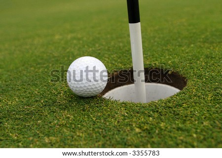 Golf ball on green close to cup with flag pole in it. - stock photo