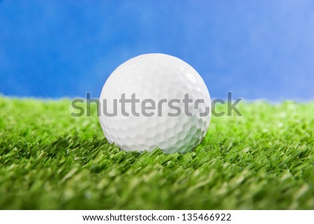 Golf ball on green field grass against blue sky - horizontal image - stock photo