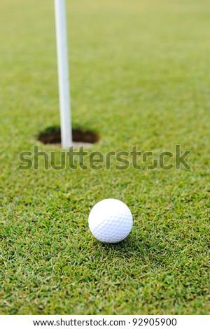 Golf ball on green grass - stock photo