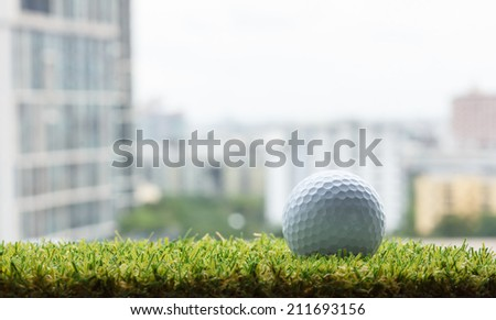 Golf ball on green grass (artificial turf) with building background - stock photo