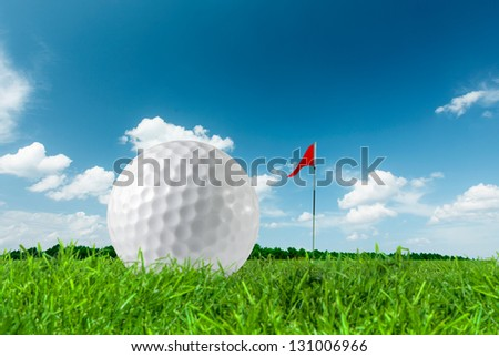 Golf ball on green grass close up and the flag - stock photo