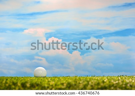 Golf ball on green grass on sky background - stock photo