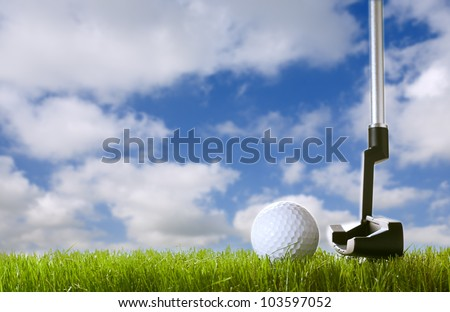 golf ball on green grass with club under sky