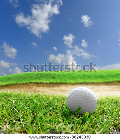 Golf ball on green grass with sand bunker - stock photo