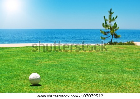 Golf ball on green grass with the ocean. Portugal. - stock photo