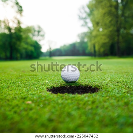 Golf ball on green meadow. golf ball on lip of cup - stock photo