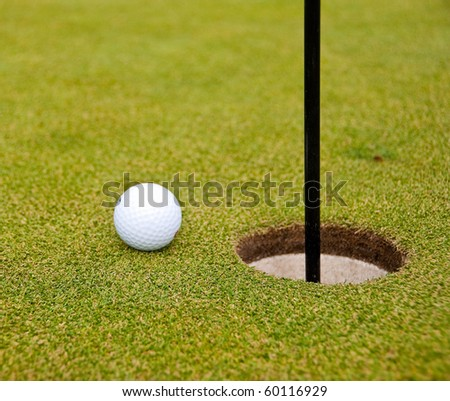 Golf ball on green with flag. Shallow depth of field. Focus on the ball and the flag. - stock photo