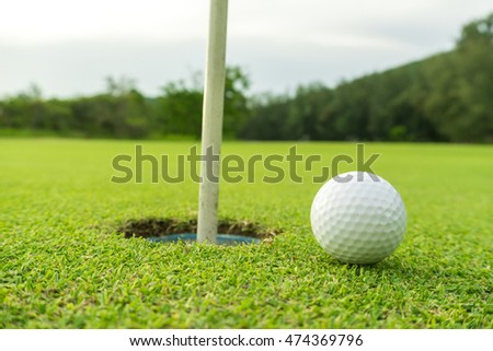golf ball on lip of cup. golf course