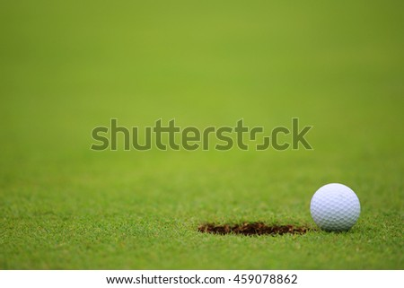 Golf ball on lip of cup on green of golf course
