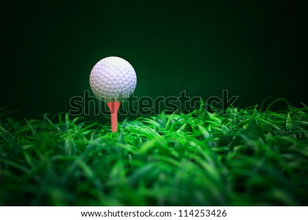 golf ball on red tee and green grass field - stock photo
