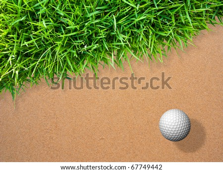 Golf ball on sand with green grass for background