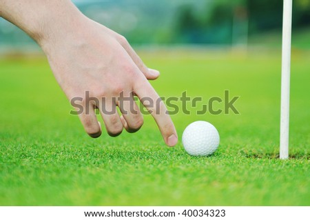 golf ball on sports golf course and hole - stock photo