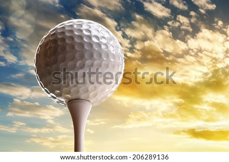 Golf ball on tee about to tee off against a sunset sky - stock photo