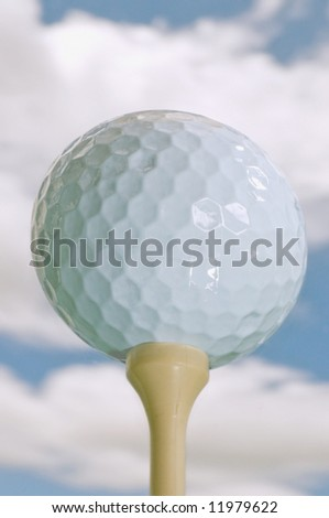 golf ball on tee isolated against blue sky with puffy clouds - stock photo