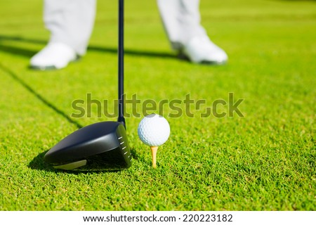 Golf Ball on Tee, Man about to Hit Ball with Driver - stock photo