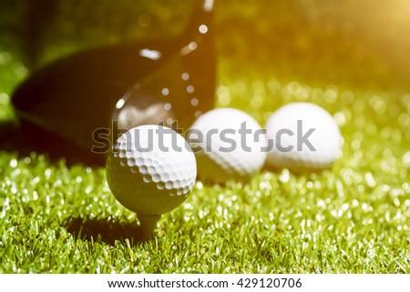 Golf ball on tee ready to be shot on sun set - stock photo