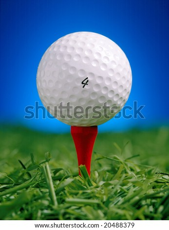 Golf Ball on Tee with blue background - stock photo