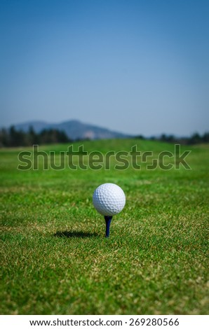Golf ball on teeing area with green grass ahead and mountains in background. Soft focus or shallow depth of field. - stock photo