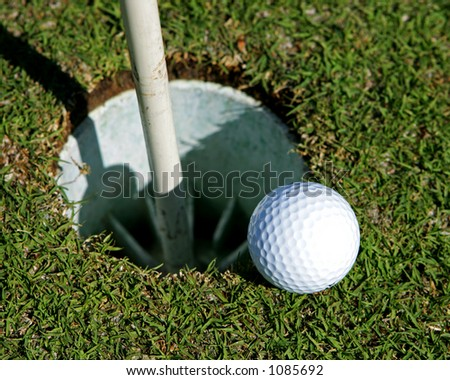 Golf Ball on the edge of a hole - stock photo