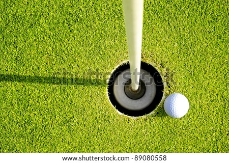 Golf ball on the edge of hole on the green grass - stock photo