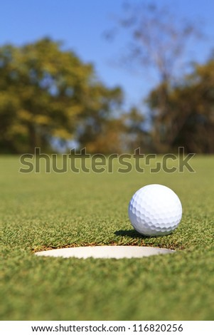 Golf ball on the edge of the hole - stock photo