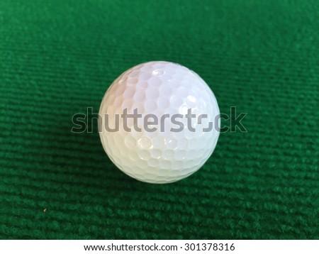 Golf ball on the green grass - stock photo